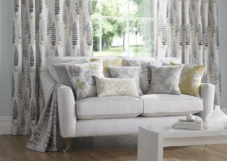 Wemyss -  Eclectic Fabric Collection - A white sofa with white, pale green and light grey patterned and floral scatter cushions and curtains, with a white table