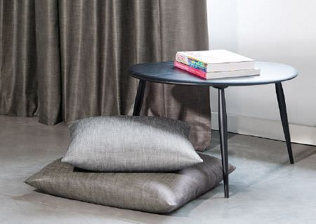 Wemyss -  Enya Fabric Collection - Shiny silver and chrome coloured scatter cushions beside chrome coloured curtains, a low, round black table and 2 books