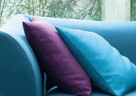 Wemyss -  Lana Fabric Collection - Two plain aqua blue and Royal purple square scatter cushions placed against the arm of a plain, bright sky blue sofa
