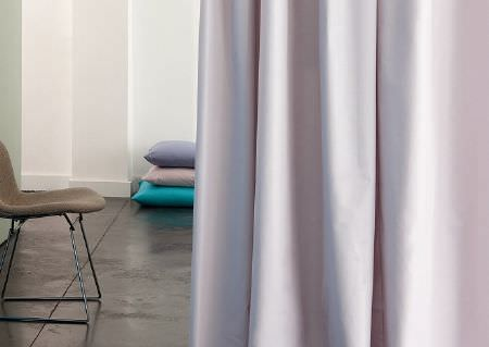 Wemyss -  Madrigal Fabric Collection - A grey seat with black metal legs, a stack of plainmauve, beige and aqua blue cushions, and very pale coloured curtains