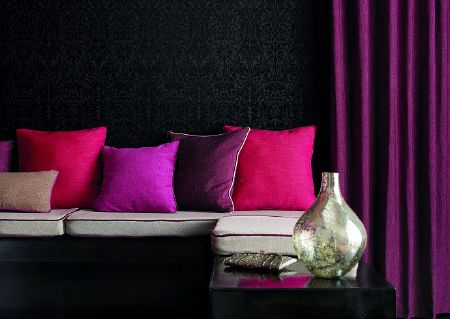 Wemyss -  More Weaves Fabric Collection - A corner sofa with grey seats, plain purple curtains, scatter cushions in bright pink and purple shades, and a silver vase