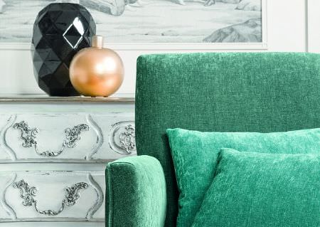 Wemyss -  Paraiso Fabric Collection - Two black androse gold vases on a distressed, carved, white wood chest of drawers, behind a plain jade coloured sofa