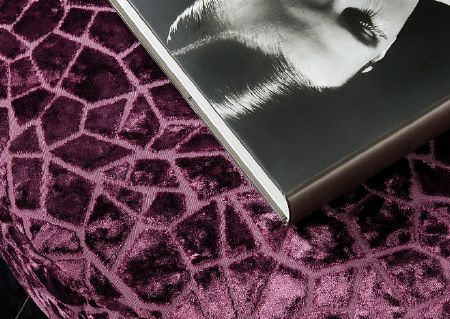 Wemyss -  Presto Fabric Collection - A book with a black and white photographic cover, placed on a velvet textured purple snakeskin patterned fabric