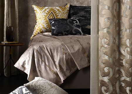 Wemyss -  Sonata Fabric Collection - A bed with a lustrous, pewter coloured throw, black and gold patterned cushions, and mocha coloured patterned curtains