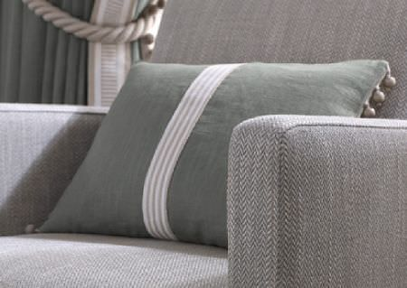Wemyss -  Talia Fabric Collection - Beige and white stripes running down a green-grey cushion with a beaded trim, on a herringbone patterned armchair