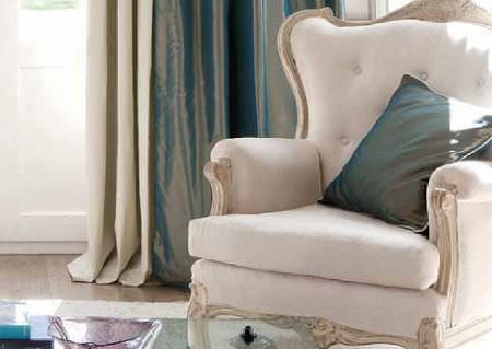 Wemyss -  Thor Fabric Collection - A grand cream padded armchair with a carved wood frame, with a shimmering peacock-cream cushion and matching curtains
