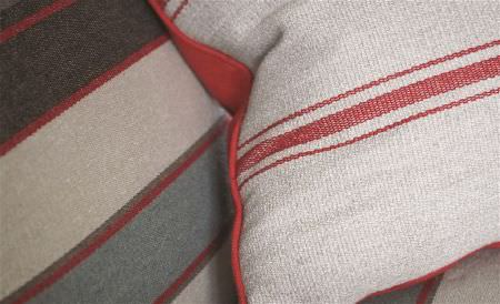 William Yeoward -  Aranjasa Weaves Fabric Collection - A paprika and cream striped cushion, placed on a dark brown-grey, light blue-grey, cream and paprika striped surface