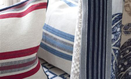 William Yeoward -  Astasia and Monsoreto Fabric Collection - Striped and patterned fabrics, next to 2 horizontally striped cushions, all made in cream and shades of red, blue and grey