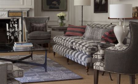 William Yeoward -  Astasia and Monsoreto Fabric Collection - Plain and checked armchairs and a sofa made in cream and dark grey, with a rug, red and grey cushions, and a coffee table