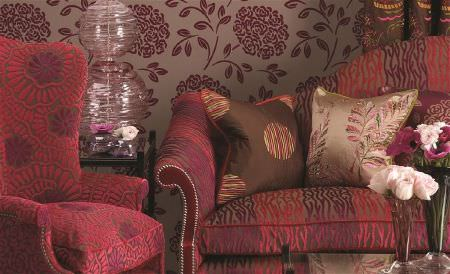 William Yeoward -  Delacroix Fabric Collection - Dark shades of red and brown making up a textured, patterned sofa and armchair, with lustrous cushions and floral walls