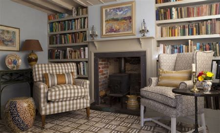 William Yeoward -  Exmere and Manton Fabric Collection - Brown and cream colours making up a patterned rug, 2 checked and patterned armchairs, with a black table and a fireplace