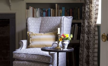 William Yeoward -  Exmere and Manton Fabric Collection - An armchair covered with a small light grey and white pattern, with a gold and cream striped cushion, and a round table