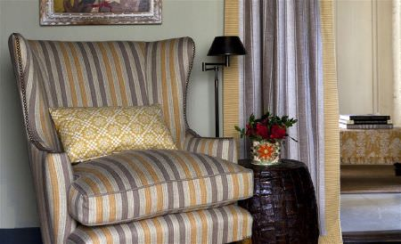 William Yeoward -  Exmere and Manton Fabric Collection - A gold, dark grey and silver striped armchair with co-ordinating curtains, a gold patterned cushion, and a dark brown table