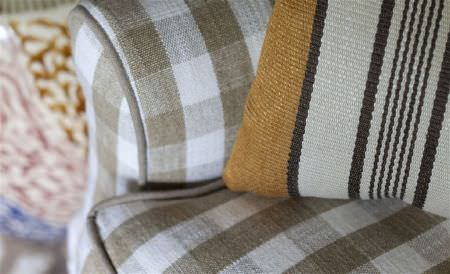 William Yeoward -  Exmere and Manton Fabric Collection - A khaki and white checked padded armchair with a woven, striped cushion in off-white, black and dark gold