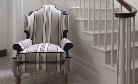 William Yeoward -  Exmere and Manton Fabric Collection - A plain white staircase beside a grand padded armchair covered with grey, black and white stripes, with black wood accents