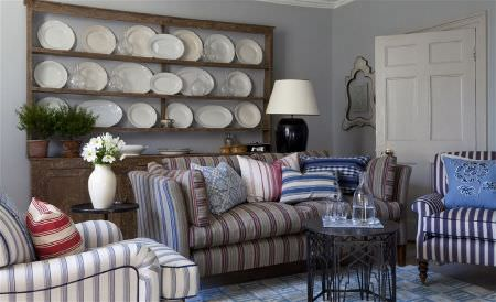 William Yeoward -  Exmere and Manton Fabric Collection - Striped sofas, armchairs and cushions ingrey, blue, white and red shades, with a black table, and plates on a wall unit