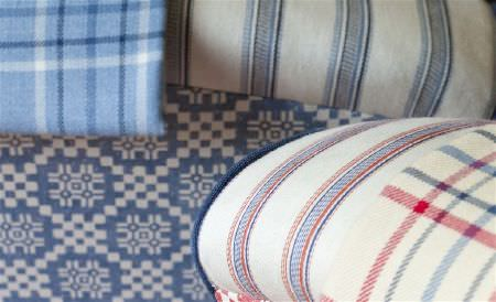 William Yeoward -  Exmere and Manton Fabric Collection - Throws draped over upholstered chairs, all made with checked, striped and patterned fabrics in red, blue and ivory shades