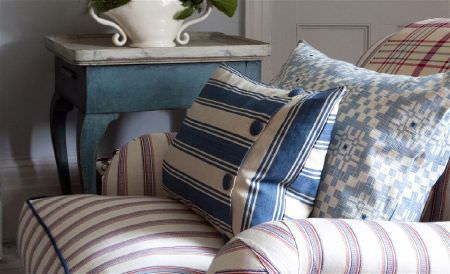 William Yeoward -  Exmere and Manton Fabric Collection - A distressed blue and white table beside a red, white and blue striped armchair with 2 striped and patterned cushions