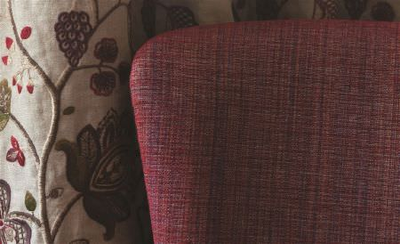 William Yeoward -  Library I Fabric Collection - Beige curtains embroidered with brown, green and red florals, behind a chair covered with semi-plain red-purple fabric