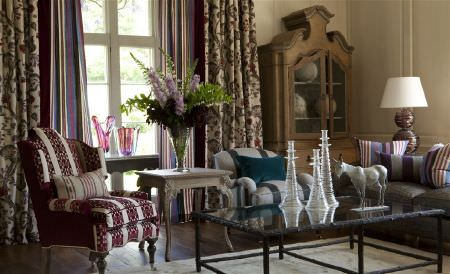 William Yeoward -  Marlena and Alberesque Fabric Collection - Floral curtains, two striped armchairs, a plain grey sofa, a black and glass table, a carved side table, and a wood cabinet