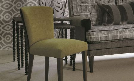 William Yeoward -  Marlena and Alberesque Fabric Collection - Grey and white patterned walls, a nest of 2 black tables, a plain green chair, a plain and checked grey sofa, and cushions