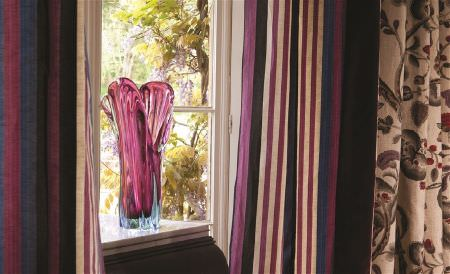 William Yeoward -  Marlena and Alberesque Fabric Collection - A magenta coloured glass vase with vertically striped curtains in jewel shades, with cream, grey and red floral curtains