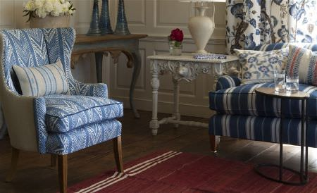 William Yeoward -  Marlena and Alberesque Fabric Collection - A striped and chevron patterned sofa and armchair in white and shades of blue, with 3 cushions, a red rug and ornate tables
