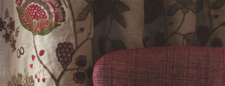 William Yeoward -  Marlena and Alberesque Fabric Collection - A chair made with fabric woven from red and purple threads, with floral embroidered curtains in beige, red, green and brown