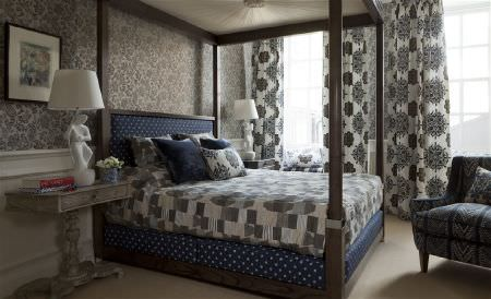William Yeoward -  Marlena and Alberesque Fabric Collection - A 4 poster bed with blue and white polka dot sheets, grey and white bedding, patterned curtains, matching walls, and a chair