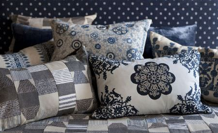 William Yeoward -  Marlena and Alberesque Fabric Collection - Plain, textured and patterned cushions in white, grey and navy blue, on a patchwork surface with a polka dot headboard