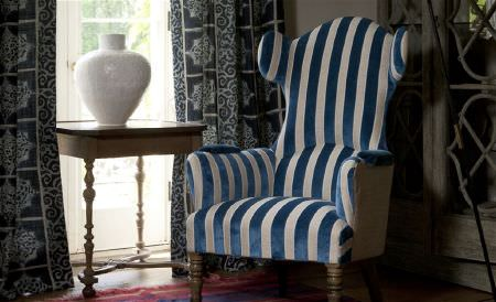 William Yeoward -  Marlena and Alberesque Fabric Collection - A grand blue and white striped armchair beside navy patterned curtains, with a painted wood side table and a white vase