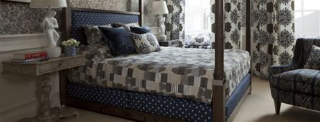 William Yeoward -  Marlena and Alberesque Fabric Collection - Grey patterned fabrics making up bedding, curtains, cushions and an armchair, with a 4 poster bed with polka dot sheets