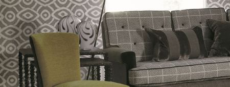 William Yeoward -  Marlena and Alberesque Fabric Collection - A grey checked sofa with striped, textured cushions, a plain green fabric chair, a nest of 2 tables, and patterned walls
