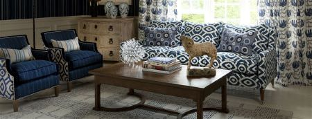William Yeoward -  Marlena and Alberesque Fabric Collection - Dark blue striped and patterned armchairs, a co-ordinating sofa, stylised floral curtains, a wooden table, and a grey rug