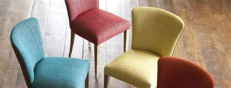 William Yeoward -  Marlena and Alberesque Fabric Collection - Four chairs with wood legs, all covered in plain fabrics: one in red, one in yellow, one in burnt orange, and one in blue
