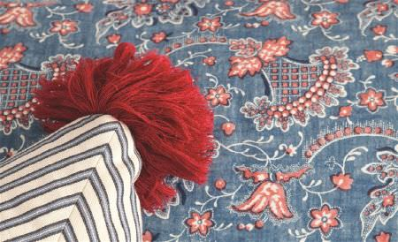 William Yeoward -  Polperro and St Mawes Fabric Collection - A red pompom on the corner of a white, blue and grey striped cushion, on a surface covered with blue, red and white patterns