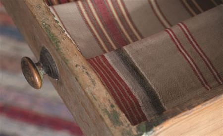 William Yeoward -  Polperro and St Mawes Fabric Collection - A distressed wooden drawer holding folds of striped fabric in rich brown, dark red, pale grey, charcoal and grey-beige