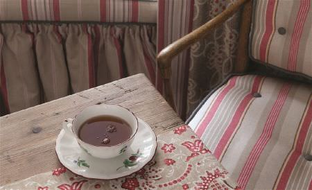 William Yeoward -  Polperro and St Mawes Fabric Collection - A red, beige and off-white striped, wood framed armchair, a matching table runner on a wood table, with a teacup and saucer