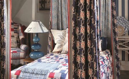 William Yeoward -  Polperro and St Mawes Fabric Collection - Navy, red and cream floral curtains at the corners of a 4 poster bed, with patterned bedding, an armchair and a large lamp