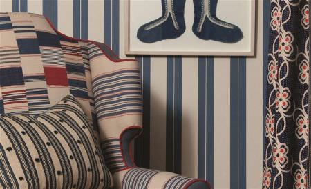 William Yeoward -  Polperro and St Mawes Fabric Collection - Blue and cream striped walls, a blue, red and cream striped armchair, a co-ordinating scatter cushion and floral curtains