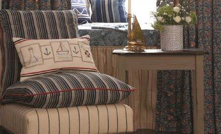 William Yeoward -  Polperro and St Mawes Fabric Collection - Dark shades of grey making up striped cushions and floral curtains, with a cream, red and grey valance, chair and cushion