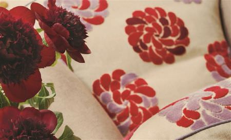 William Yeoward -  Ranakpur Fabric Collection - Red flowers placed with cream coloured fabrics featuring red, burgundy and mauve flowers which are stylised and textured