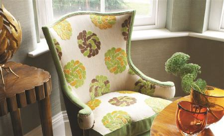 William Yeoward -  Ranakpur Fabric Collection - Textured, stylised green, mustard and brown florals on a cream armchair, by a chunky wood table and a round, polished table