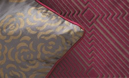 William Yeoward -  Valois Fabric Collection - A lustrous gold and pewter floral cushion and a dark brown surface featuring a velvet textured burgundy geometric design
